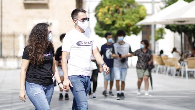 Dos personas con mascarilla caminan por la Plaza de España de Mérida.