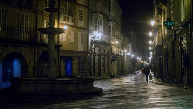 Un hombre, con una bolsa y un juguete, camina por la Plaza del Hierro de Ourense, cuando entró en vigor el estado de alarma decretado por el Gobierno, que incluye un toque de queda desde las 23.00 a las 6.00.