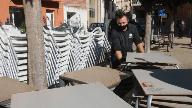 El propietario de un bar recoge las sillas y mesas de la terraza tras el cierre decretado por la Generalitat, el pasado 16 de octubre.
