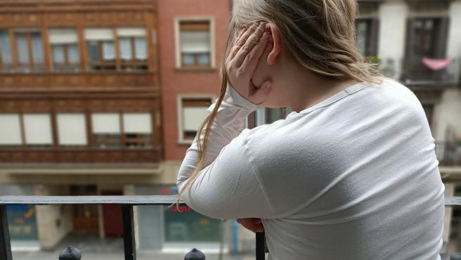 Imagen de una niña asomada al balcón durante el confinamiento por el estado de alerta