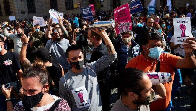 Decenas de personas piden en la plaza Sant Jaume de Barcelona levantar el cierre de la restauración.