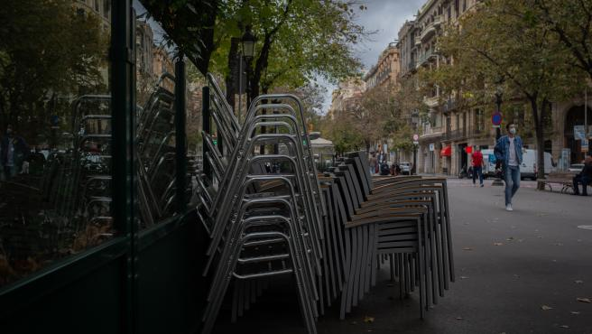Sillas recogidas de una terraza de un bar de Barcelona cerrado por las nuevas restricciones en Cataluña.