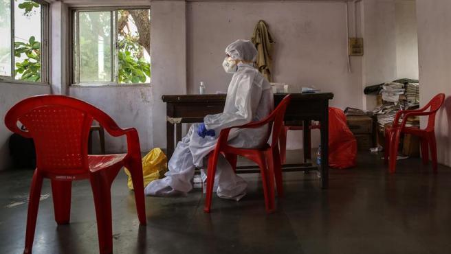 Un trabajador sanitario espera la llegada de un grupo de policías para realizarles test de coronavirus, en una comisaría de Bombay, India.