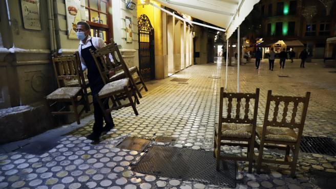Un camarero recoge la terraza del bar ubicado en Málaga.