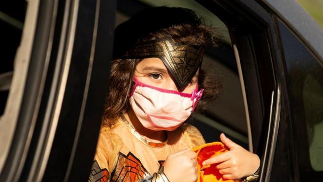 Una niña con mascarilla por la pandemia del coronavirus, durante una fiesta de Halloween organizada en Monterey Park, California (EE UU).