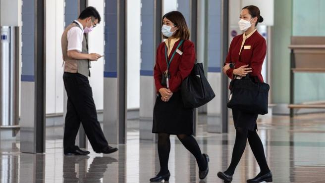 Dos azafatas de Cathay Pacific, con mascarillas por el coronavirus, en el aeropuerto internacional de Hong Kong, China.