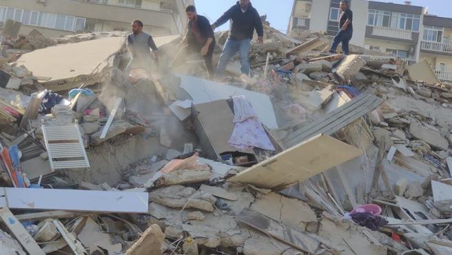varios hombres sobre un edificio derrumbado tras el terremoto. Según informes de medios turcos, decenas de edificios fueron destruidos por el terremoto.