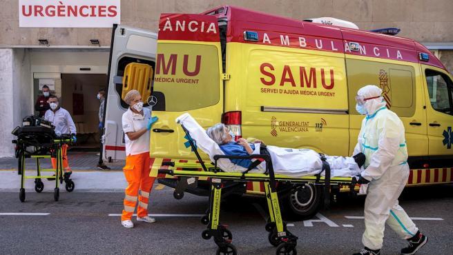 Sanitarios con equipo de protección especial trasladan a un paciente de una ambulancia a urgencias del Hospital Clínico de València.