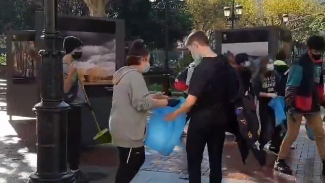 Varios jóvenes limpiando las calles tras lo sucedido.