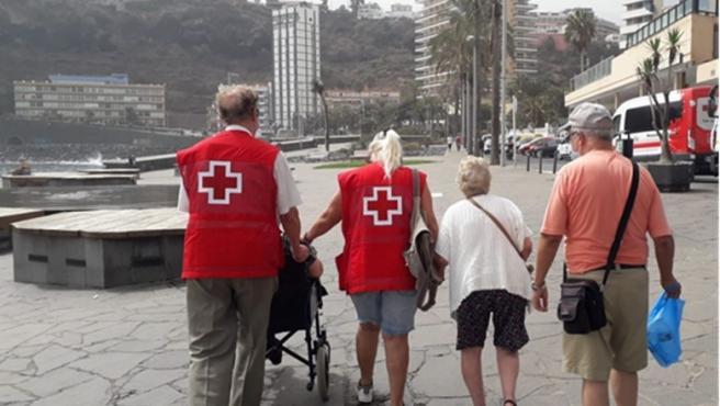 Un cuidador y dos personas mayores a su cargo dan un paseo en Puerto de la Cruz, acompañados por dos voluntarios del proyecto de Cruz Roja