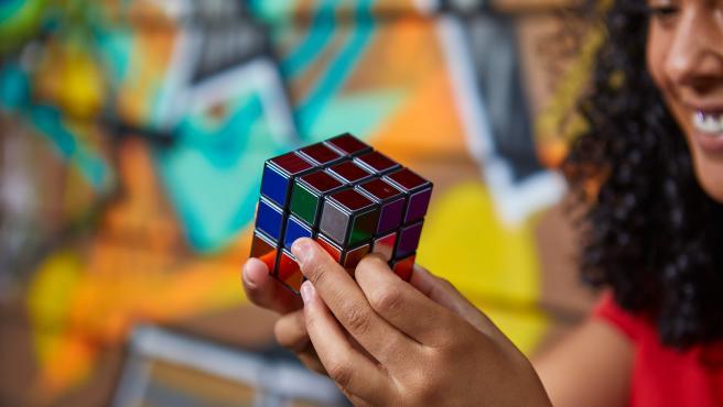 Una joven juega con el Cubo de Rubik.