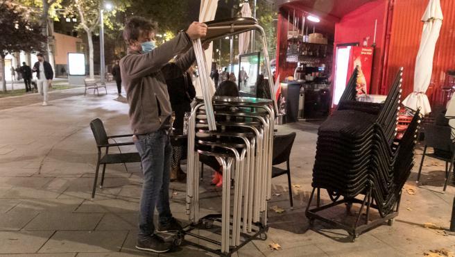 Un hostelero recoge su terraza en Zaragoza.