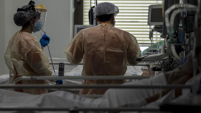 Dos sanitarios atienden a un paciente en la UCI dedicada a enfermos de coronavirus del Hospital Ramón y Cajal, en Madrid.