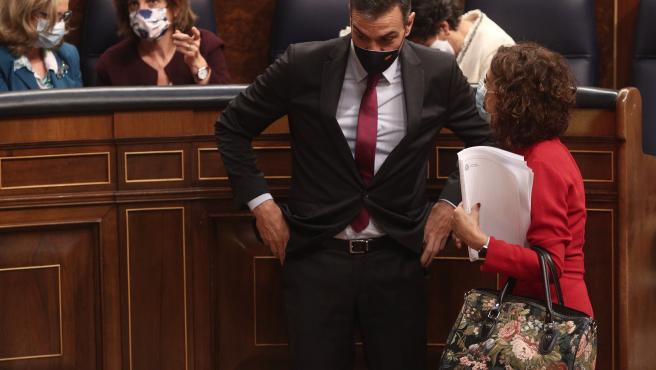 El presidente del Gobierno, Pedro Sánchez, conversa con la ministra de Hacienda, María Jesús Montero (d), al término de la primera parte del pleno de Debate de totalidad del Proyecto de Ley de Presupuestos Generales del Estado para el año 2021.