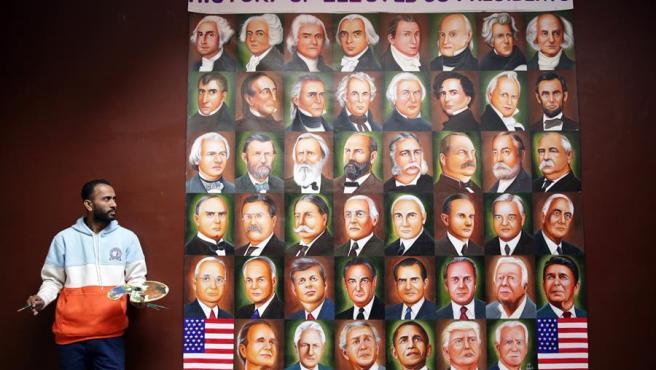 El artista indio Jagjot Singh Rubal posa junto a su obra, un mural con los rostros de los 46 presidentes de Estados Unidos, incluido el actual presidente electo, Joe Biden.