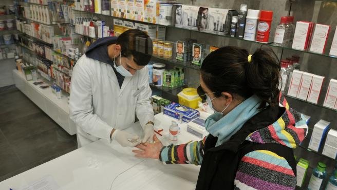 Un farmacèutic realitza una prova serológica de Covid-19 en la Farmàcia Mónica Emmurallades, en O Carballiño, Orense