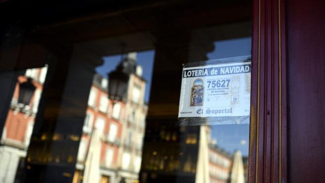 Décimo del Sorteo Extraordinario de la Lotería de Navidad 2020 pegado en el escaparate de un restaurante de la Plaza Mayor