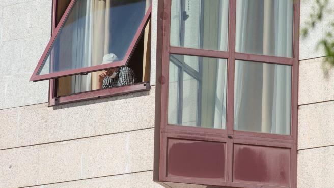 Un anciano se asoma a una venta en una residencia