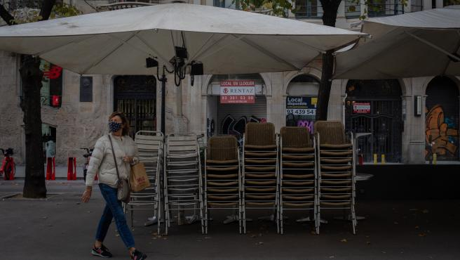 Una mujer pasa junto a la terraza recogida de un bar cerrado durante el cuarto día de la entrada en vigor de las nuevas restricciones en Cataluña, en Barcelona, Cataluña (España) a 20 de octubre de 2020. El pasado viernes 16 de octubre entraron en vigor l