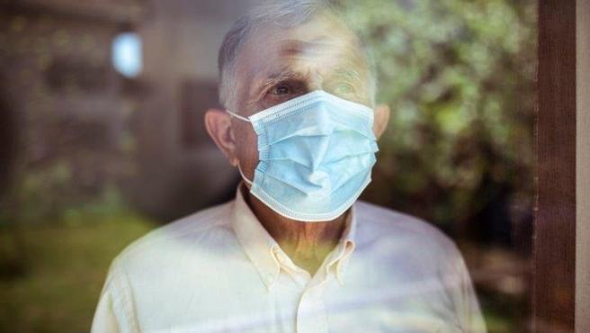 Un hombre mayor con mascarilla mira por la ventana.