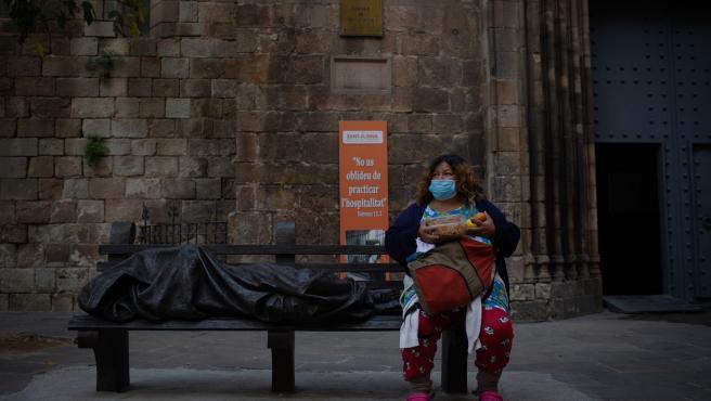 Una persona sin techo come en zonas exteriores de las instalaciones del hospital de campaña perteneciente a la parroquia de Santa Anna, en Barcelona.
