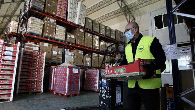 Un voluntario, en el almacén que el Banco de Alimentos de Madrid tiene en San Fernando.