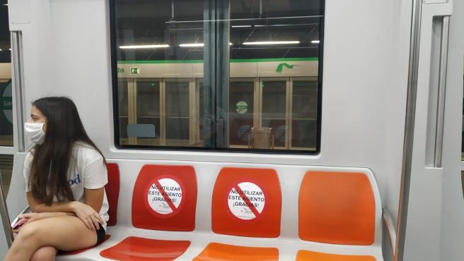 Una joven con mascarilla viaja en el Metro de Sevilla