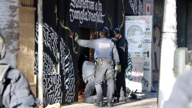 Los Mossos trabajan con una radial para entrar en la casa okupa La Engorilada de Barcelona.