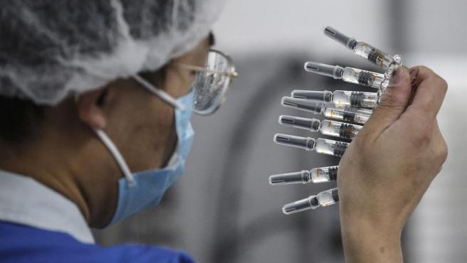 Un trabajador realiza tareas de control de calidad de la vacuna china del fabricante Sinovac.