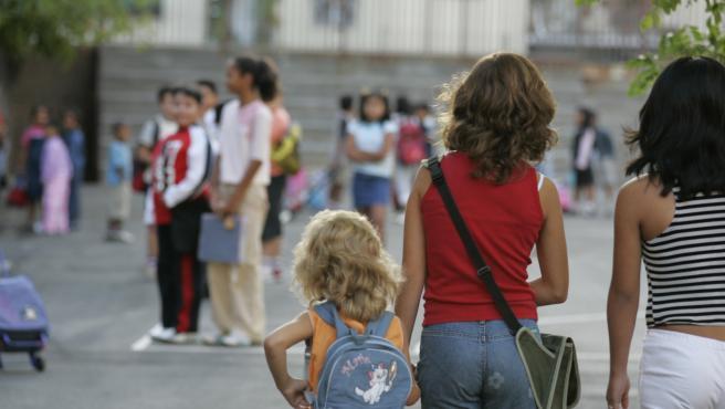 Un grupo de menores en el patio de un colegio.