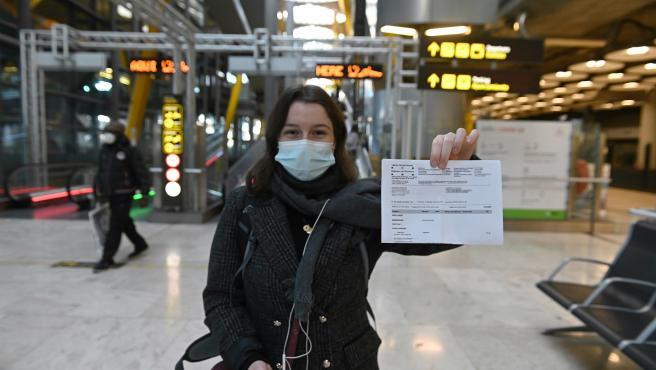 Una joven muestra el resultado de su PCR a su llegada al aeropuerto Adolfo Suárez-Barajas en Madrid.