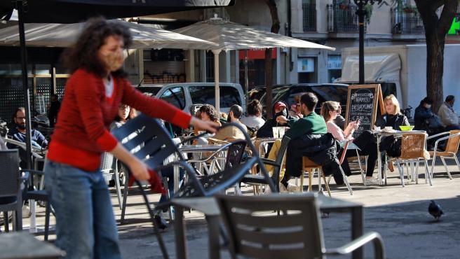 La propietaria de un bar de Barcelona monta la terraza en el primer día de reapertura de la restauración en Catalunya.