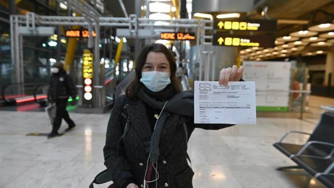 Una joven muestra el resultado de su PCR a su llegada al aeropuerto Adolfo Suárez-Barajas en Madrid, este lunes, donde comienza la exigencia de pruebas PCR para pasajeros de vuelos procedentes de países de riesgo.