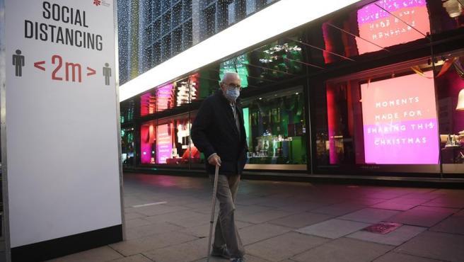 Un hombre con mascarilla por el coronavirus pasa junto a tiendas con decoración navideña en Londres, Reino Unido.