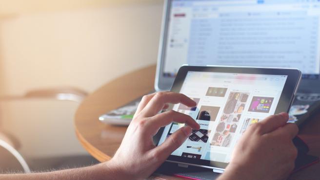 Una persona utilizando una tablet junto a un ordenador portátil