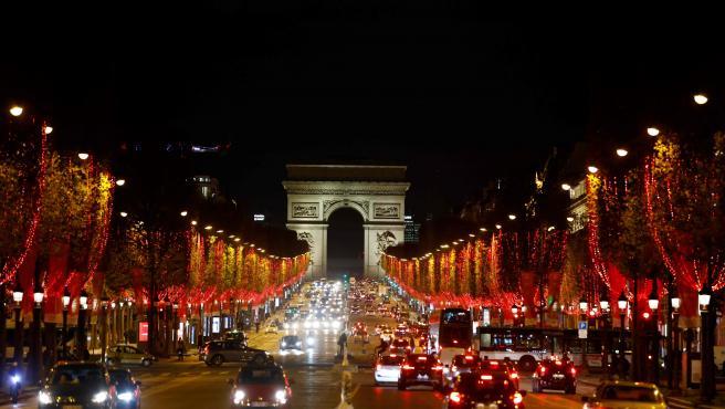 La avenida de los Campos Elíseos se ilumina en rojo al encenderse las luces de Navidad en París (Francia).
