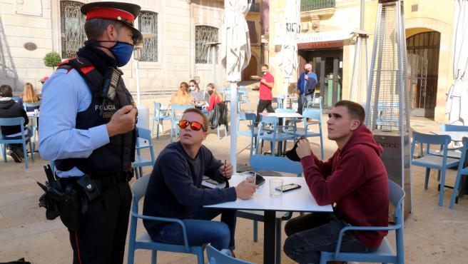 Un agente de los Mossos pidiendo este miércoles a dos chicos que se pongan la mascarilla mientras no consumen en una terraza de Tarragona.
