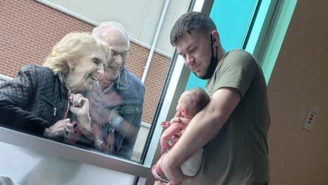 Unos abuelos conociendo a su nieto recién nacido a través de un cristal.