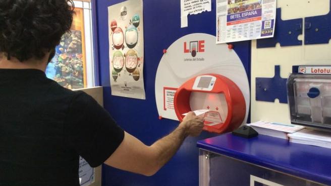 Una persona comprueba su boleto en una administración de Loterías.