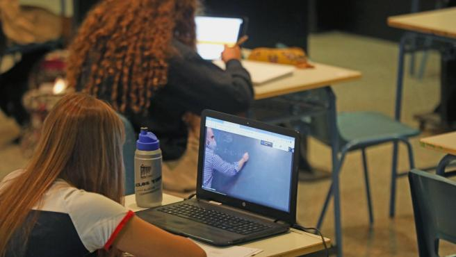 Dos alumnas asisten desde su ordenador a clases virtuales.