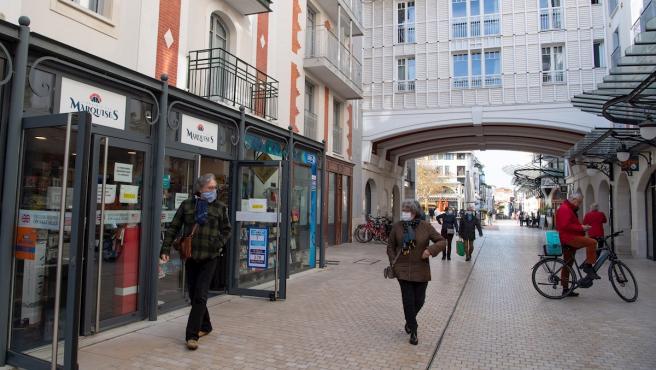 Varios viandantes pasean mirando las tiendas abiertas en las calles de Arcachon, al suroeste de Francia.