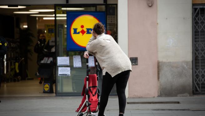 Imagen de archivo de una mujer esperando con su carro de la compra fuera de un supermercado Lidl.