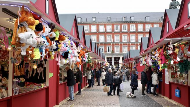 Varios madrileños pasean por el mercadillo de Navidad de la Plaza Mayor.