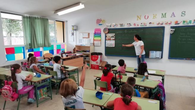 Una profesora da clases a alumnos de Primaria en un colegio.