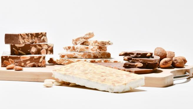 Close up of an assortment of delicious almond nougat chunks on a wooden cutting table surrounded by almonds on a light background. Sweets concept.