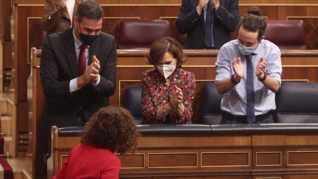 (El presidente Pedro Sánchez y los vicepresidentes Carmen Calvo y Pablo Iglesias aplauden a la ministra de Hacienda, Maria Jesús Montero.