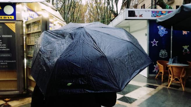 Un hombre pasea por la Rambla de Palma bajo un paraguas un día de lluvia.