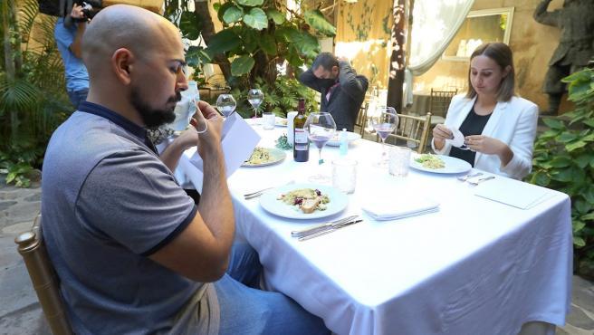 Cuatro voluntarios realizan un simulacro sobre las pautas contra la Covid que hay que seguir a la hora de sentarse a la mesa y servir la comida y el vino.