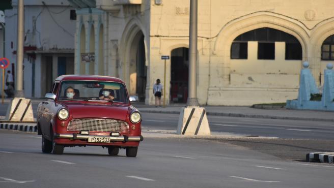Dos personas con mascarillas en un coche por las calles de La Habana.