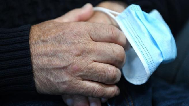 Una persona mayor toma una mascarilla entre sus manos